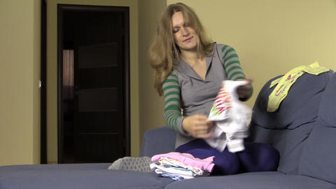 Pregnant woman packing hospital bag. Preparing for baby birth Footage