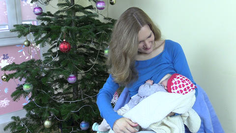 Happy mother breastfeed feed infant baby near Christmas tree Footage