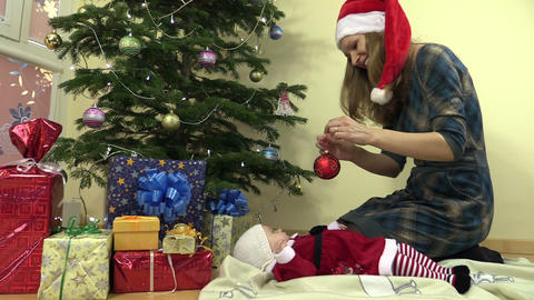 mother hang christmas tree toy. infant baby in christmas dress Footage