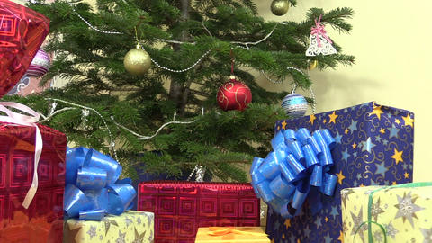 Colorful gift present box with ribbon under cute christmas tree Footage