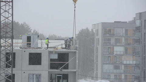 Snow fall and construction site workers build house in winter Footage