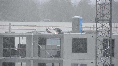 Blizzard snow fall and welder work in construction site Footage