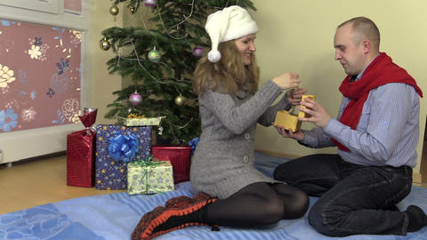 Couple man and woman exchange Christmas presents gifts Footage