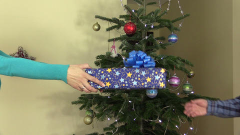 Woman hands gift for man on Christmas tree with toys background Footage