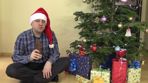 Middle age man eat delicious Santa form chocolate in Christmas Footage