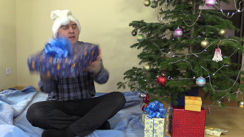 Funny family man catch gift box and put under Christmas tree Footage