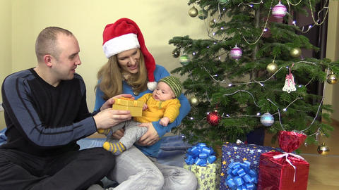 Cheerful family man and woman present gift for baby in Christmas Footage