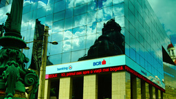 BUCHAREST, ROMANIA - June 2015,CEC Palace Mirrored In A Modern Building,Pan stock footage
