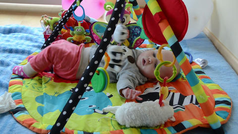 Newborn cute baby play between toys on colorful development mat Footage
