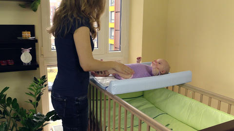mother make therapeutical massage for child lie on swaddle board Footage