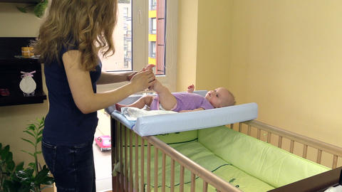 mother make therapeutic foot massage for baby on swaddle board Footage