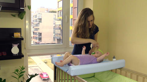 baby lie on changing table. Mother comb child hair with brush Footage