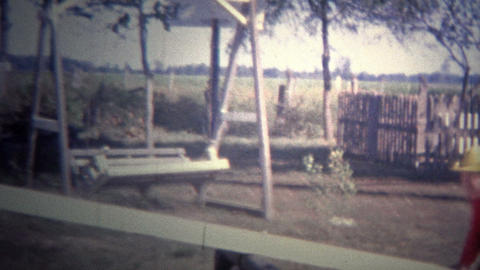 ARKANSAS, USA - 1964: Kids playing on a old teeter-totter in the front yard of t Footage