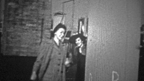 NEW YORK CITY - 1943: People coming out from a rooftop staircase to say hello Footage