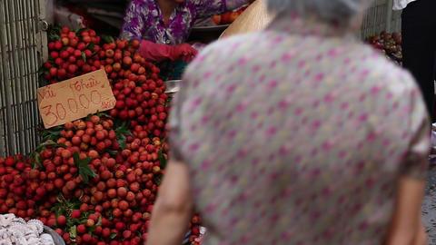 woman in rice hat picks fruit at morning market Footage