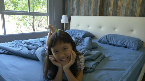 Slow motion of cute little Asian girl jumping on the bed Footage