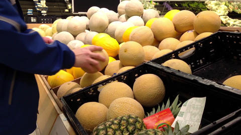 Man selecting sweet melon in grocery store produce department Footage