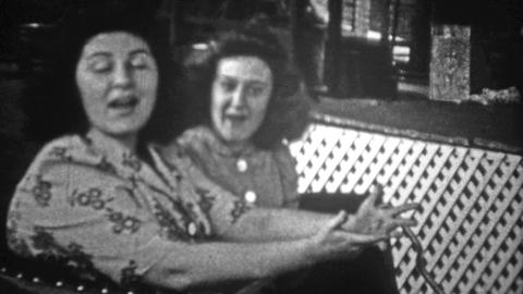 NEW YORK CITY - 1946: Women riding the Coney Island attraction Tilt A Whirl ride Footage