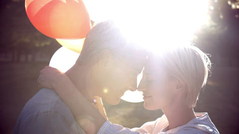 Romantic couple with balloons in park Footage