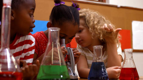 Cute pupils in classroom doing chemistry Footage