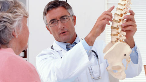 Doctor explaining a spine model to patient Footage