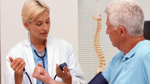 Doctor taking blood pressure of elderly patient Footage