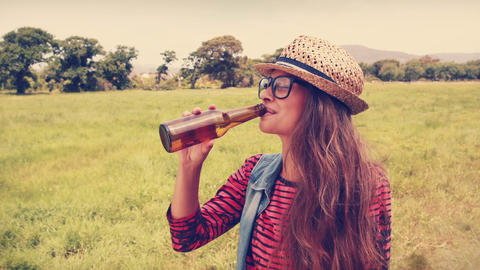Happy hipster drinking beer in the park Live Action
