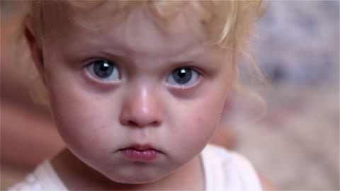 Closeup of a head of the baby with white hair and blue eyes. The girl less than  Footage