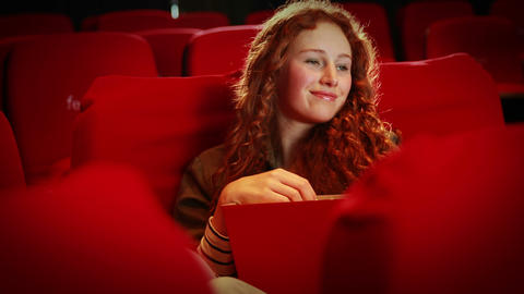 Young woman watching a movie ビデオ