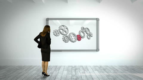 Businesswoman watching cog and wheel on wall Animation