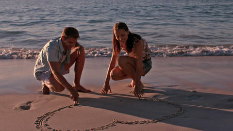 Happy couple drawing heart in the sand Footage