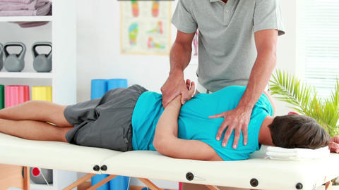 Physiotherapist giving sports massage to patient Footage