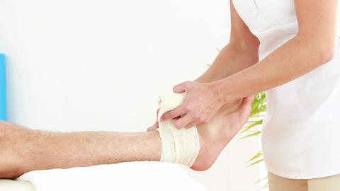Physiotherapist wrapping injured ankle in bandage Footage