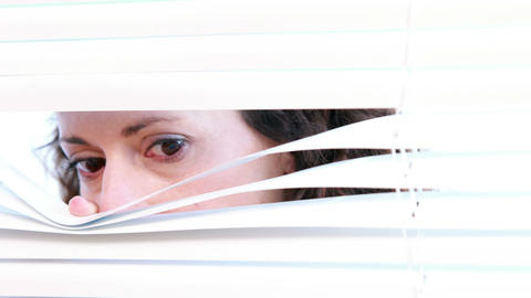 Woman peering through roller blind Footage