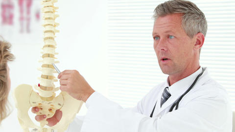 Physiotherapist Explaining Spine Model To Patient stock footage