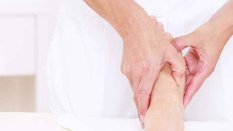 Physiotherapist doing foot massage to her patient Live Action