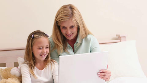 Mother And Daughter Using Laptop Together On Bed stock footage