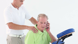 Doctor Massaging His Patients Shoulders While He Calling stock footage