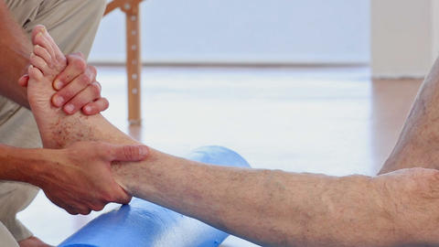 Doctor Massaging His Patients Ankle stock footage