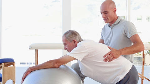 Doctor Helping His Patient To Stretch With Exercise Ball stock footage
