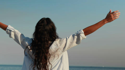 Happy woman with arms outstretched at the beach Footage