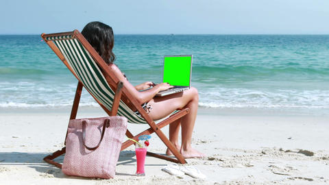 Pretty brunette using laptop on deck chair Footage