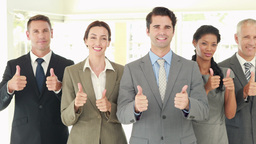 Smiling business people looking at camera gesturing thumbs up Footage