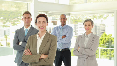 Happy business team smiling at camera with arms crossed Footage