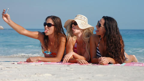 Happy pretty friends lying on towel and taking a selfie at the beach Footage