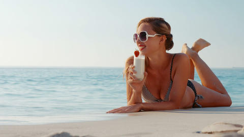 Happy pretty blonde lying on sand and drinking cocktail Footage