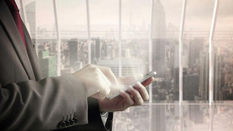 Businessman using smartphone with skyscraper on background Animation