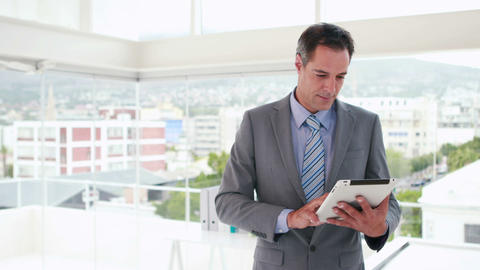 Serious businessman using tablet computer Footage