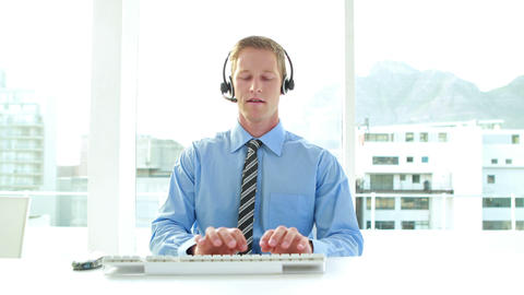 Businessman having a phone call with headset in call center Live Action