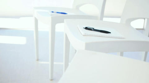 Notebook with pen on white chair Live Action